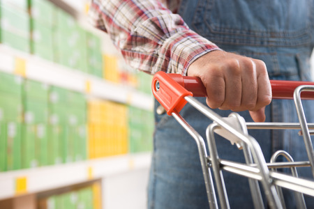 Man in dungarees and checked shirt with trolley at supermarket, hands close-up. photo