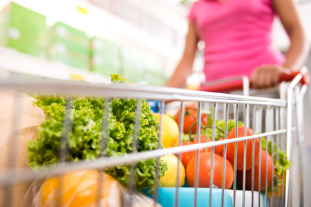 Woman at supermarket pushing a shopping cart filled with fresh fruit and vegetables. Banque d'images