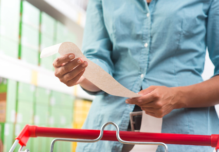 Unrecognizable woman in light blue shirt checking a long grocery receipt at store. photo