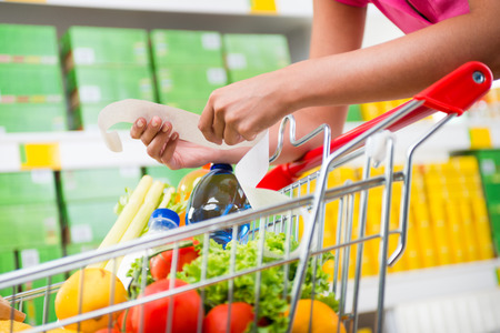Unrecognizable woman checking a long grocery receipt leaning to a full shopping cart at store. Stock Photo