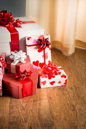 Plenty of elegant christmas gifts on hardwood floor in white and red tones. photo