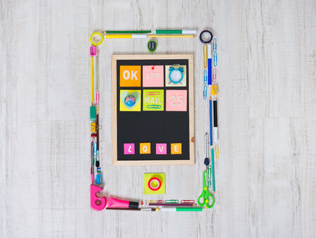 stationery items: Creative smartphone composed of colorful stationery items on the floor.