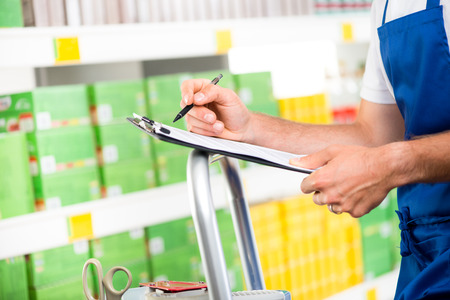 Supermarket clerk at work holding pen and clipboard with shelf on background, hands close-up. photo