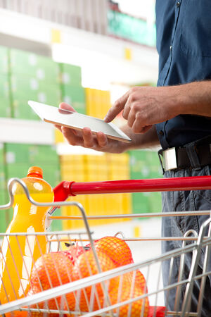 Man using digital tablet at supermarket with trolley and shelves on background. photo