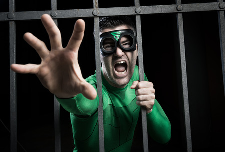 imprison: Angry green superhero shouting behind steel prison bars.