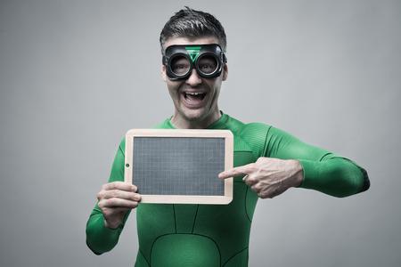 invincible: Cheerful green superhero pointing to an empty blackboard. Stock Photo