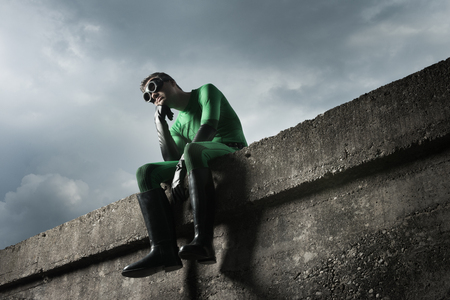 strong chin: Pensive green superhero with hand on chin and cloudy dramatic sky on background.