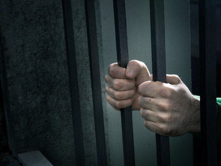 Man in jail hands close-up, depression and despair concept.