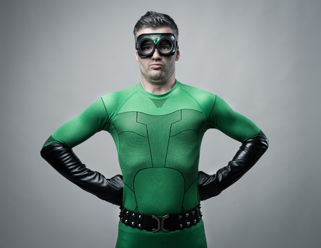 costume: Disappointed funny superhero grimacing and looking at camera.