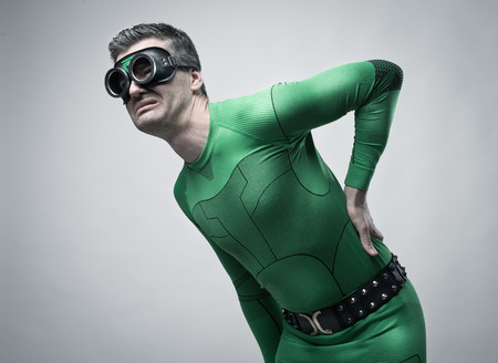 fictional character: Sad superhero bent over with back pain touching his head and back. Stock Photo