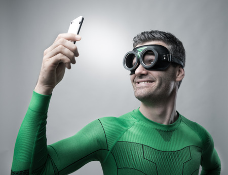 Cheerful superhero smiling and taking a selfie with a smartphone. Stock Photo