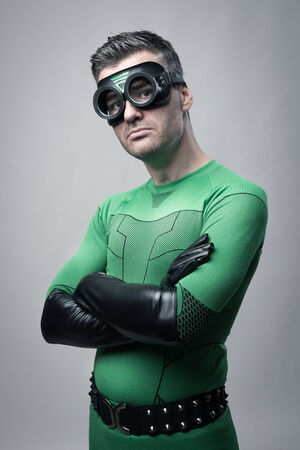 Cool superhero posing in green costume with arms crossed. Stock Photo