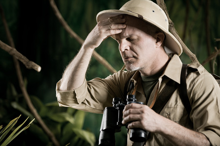 Explorer in the jungle with headache touching his temples. photo