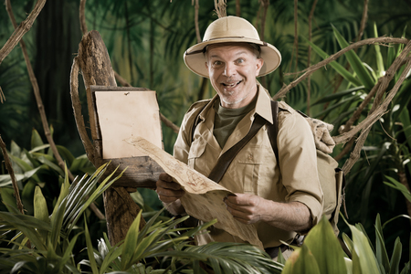 Cheerful vintage explorer in the jungle with map and blank sign. photo