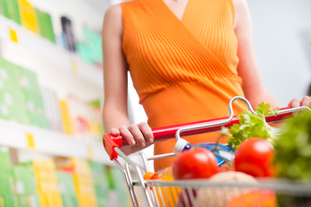 Woman shopping at supermarket, hands on trolley close-up. photo