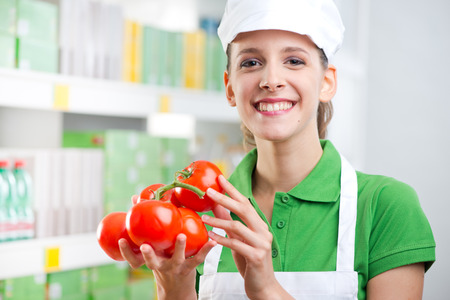 Young female sales clerk smiling and holding fresh tomatoes at supermarket. photo