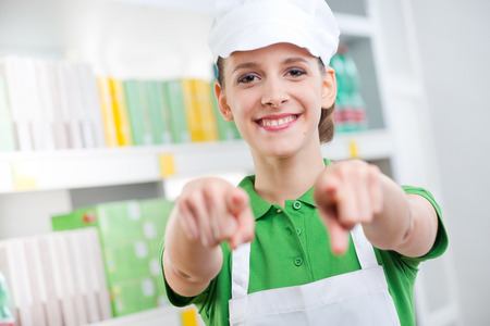 sales clerk: Young female sales clerk at supermarket smiling and pointing at camera. Stock Photo