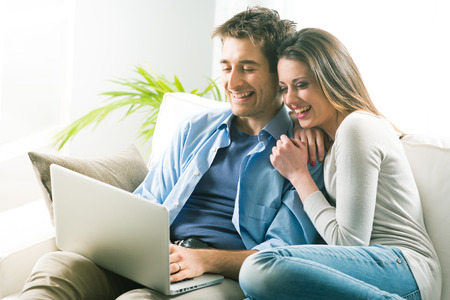 young couple smiling: Young couple relaxing on sofa with laptop in the living room. Stock Photo