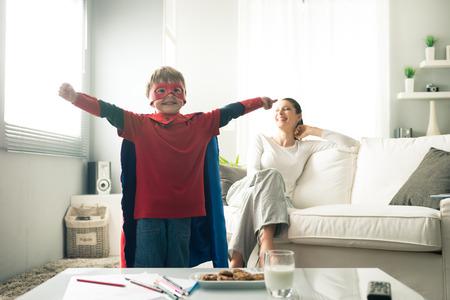 Superhero boy, die eine gesunde Zwischenmahlzeit mit Cookies und Milch mit seiner Mutter auf Hintergrund.