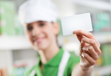 Female sales clerk holding a white card and smiling with supermarket shelf on background. photo