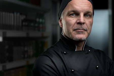 Attractive chef portrait in black uniform on dark background.