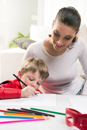 colour pencils: Mother and superhero child playing and drawing together in the living room.