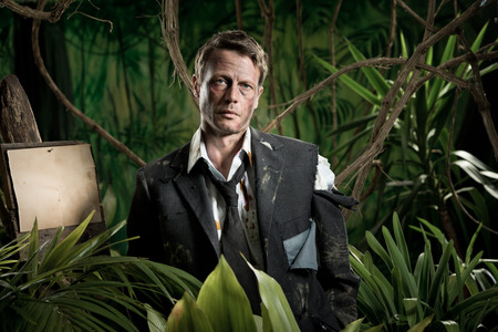 business survival: Lost scared businessman standing in the jungle in torn dirty clothing.