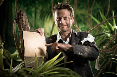 office wear: Confident smiling businessman in the jungle pointing at sign. Stock Photo