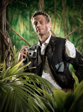photojournalist: Attractive man in torn clothing walking in jungle with vintage camera.
