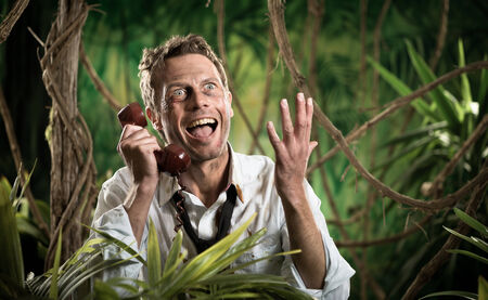 Angry businessman lost in jungle screaming at the phone and gesturing. photo