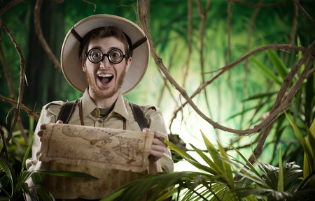 Young smiling explorer in the jungle with thick glasses holding a map. Reklamní fotografie
