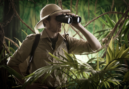 finding: Expert explorer in the jungle looking away through binoculars.