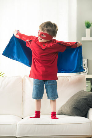 attitude boy: Superhero boy standing on sofa with arms raised showing his superpowers. Stock Photo