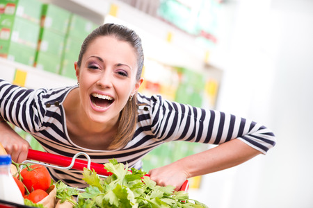 trolley: Attractive young woman smiling and pushing a cart at supermarket.
