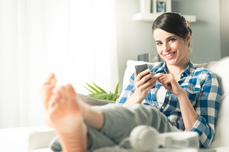 Attractive smiling woman lying on sofa and using mobile in the living room. photo