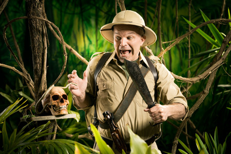 Shocked adventurer finding a human skull in the jungle with retro colonial style equipment. photo