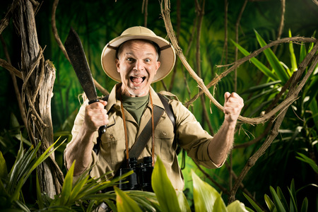 adventurer: Cheerful adventurer with machete and fists raised in the jungle. Stock Photo