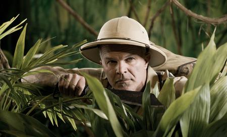 Survival confident adventurer exploring the rainforest jungle holding a machete. photo
