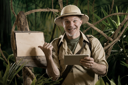 adventurer: Colonial style adventurer with digital tablet exploring jungle wilderness.