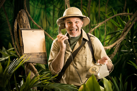 stunned: Stunned explorer having a phone call in the jungle next to a blank sign.