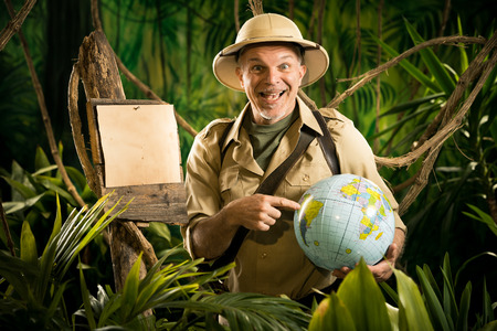 Cheerful explorer in the jungle pointing to a globe next to a wooden sign. photo