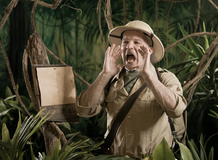 hands cupped: Explorer shouting in the forest with hands cupped around mouth and empty sign.