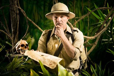 médula: Pionero de estilo colonial en la selva examinar un viejo mapa y la búsqueda de la dirección correcta. Foto de archivo
