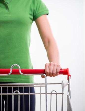 carro supermercado: Mujer joven con el carro de compras en supermercados manos primer plano.