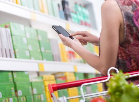 tiendas de comida: Mujer irreconocible en la tienda que usa smartphone con estantes en el fondo.