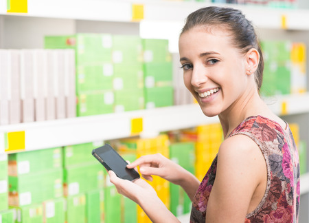 groceries shopping: Smiling young woman at supermarket using mobile phone and looking at camera.