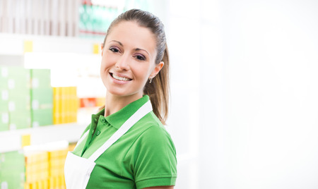 Young smiling saleswoman wearing apron, supermarket shelf on background.