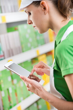 Young female sales clerk working with digital tablet at supermarket. photo