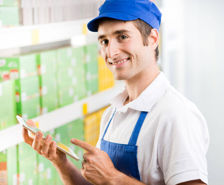 sales clerk: Young sales clerk holding a digital tablet and working at supermarket