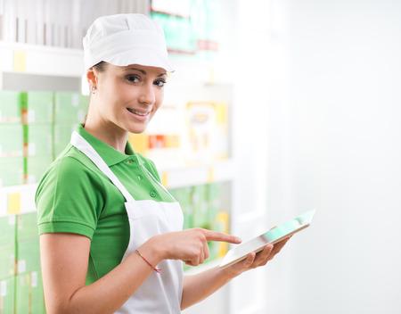oficinista: Hembra sonriente empleado de ventas que sostiene una tableta digital en el supermercado. Foto de archivo
